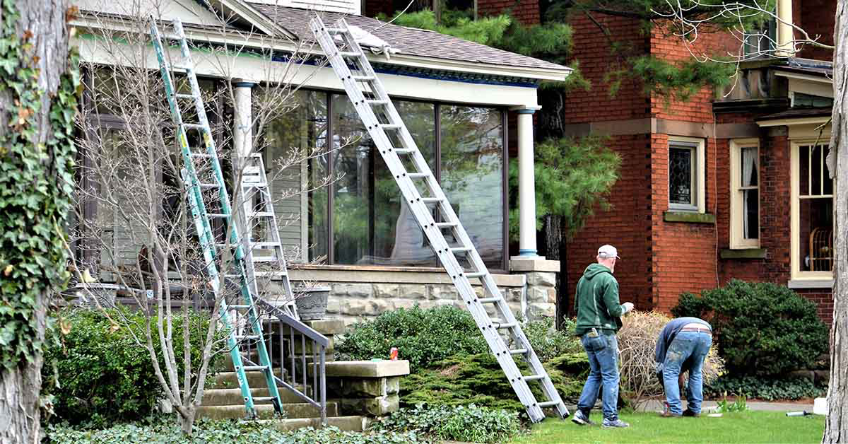 Ladders leaning against house with  men preparing for weather and completing home improvement projects.